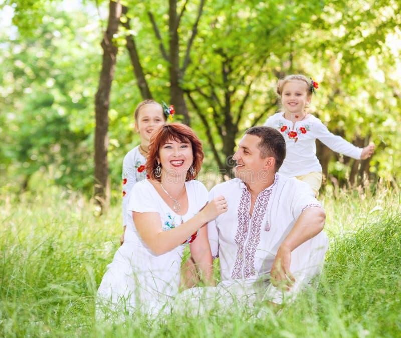 Los jóvenes se juntan con las pequeñas hijas en el parque del verano fotografía de archivo