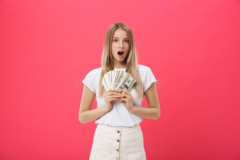 Los jóvenes sorprendieron al estudiante de mujer chocado con la boca abierta que llevaba a cabo porciones del paquete de dólares, imagen de archivo libre de regalías