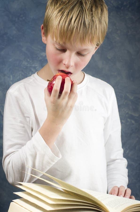 Los jóvenes sorprendieron al muchacho que leía un libro con la manzana sana roja en su ha fotos de archivo