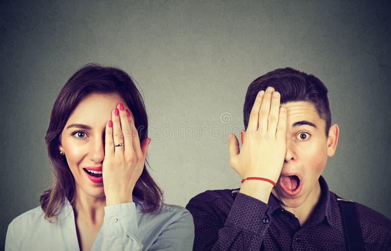 Los jóvenes sorprendieron el hombre y a la mujer de los pares que miraban la cámara fotos de archivo