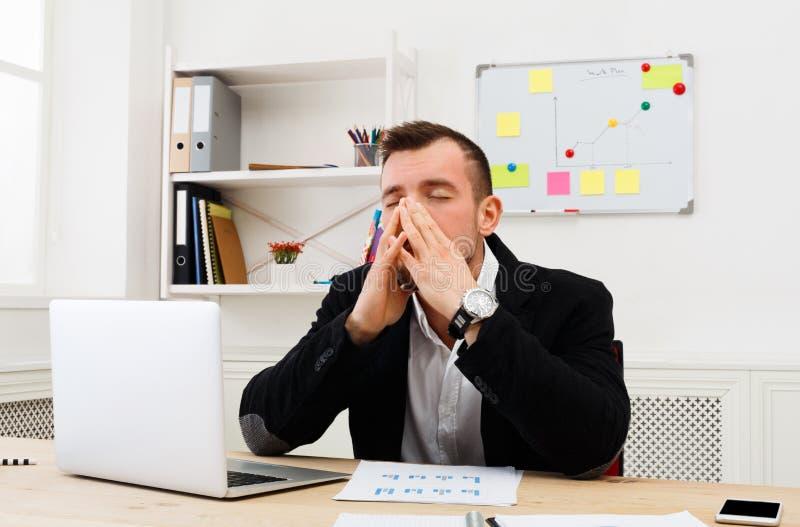 Los jóvenes subrayaron al hombre de negocios con el ordenador portátil en oficina blanca moderna imagenes de archivo