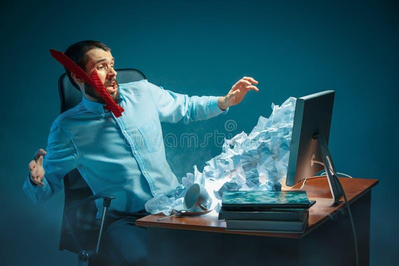 Los jóvenes subrayaron al hombre de negocios hermoso que trabajaba en el escritorio en la oficina moderna que gritaba en la panta fotos de archivo libres de regalías