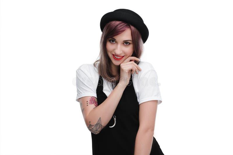 Los jóvenes tatuaron a la muchacha tímida con el pelo púrpura que sonreía en la cámara imágenes de archivo libres de regalías