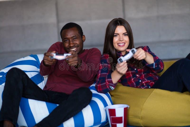 Los j?venes juntan en casa jugar al videojuego juntos fotografía de archivo