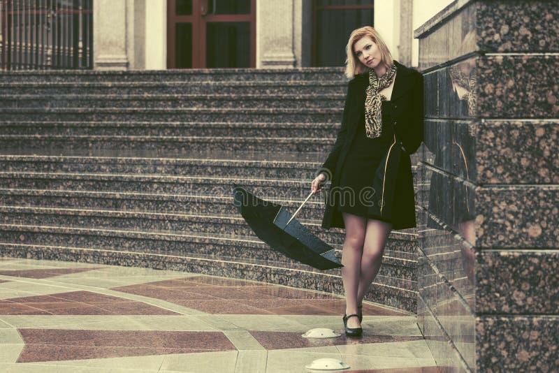 Los j?venes tristes forman a la mujer con el paraguas en la calle de la ciudad imagenes de archivo