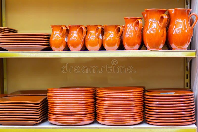 Los jarros y las placas de cerámica de la loza están en el estante de una tienda foto de archivo libre de regalías