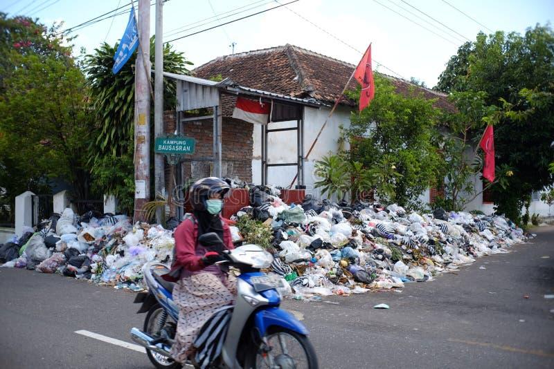 Los jinetes de la moto pasan a través de una pila de basura plástica y de basura orgánica en el borde de la carretera imagen de archivo libre de regalías