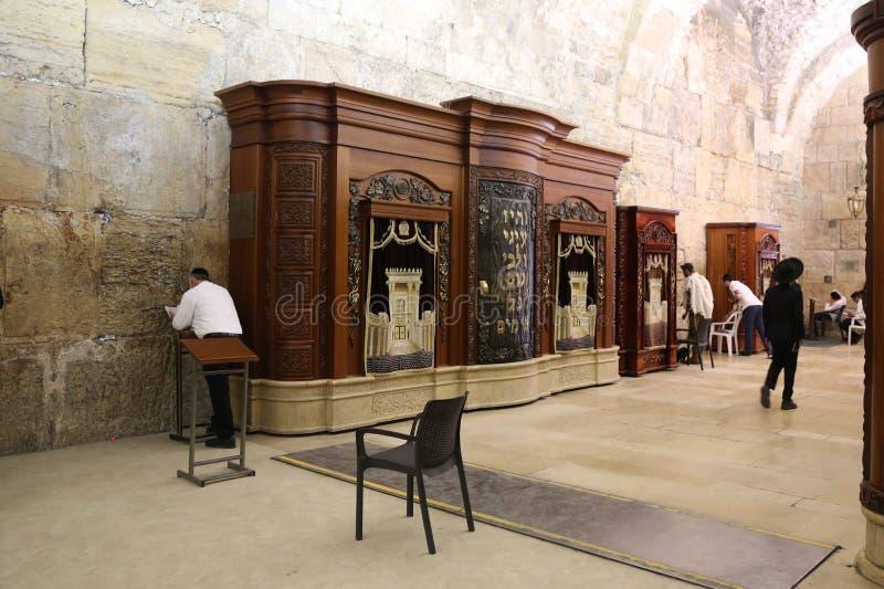Los judíos religiosos ruegan por la pared occidental dentro del túnel occidental de la pared en la ciudad vieja de Jerusalén imágenes de archivo libres de regalías