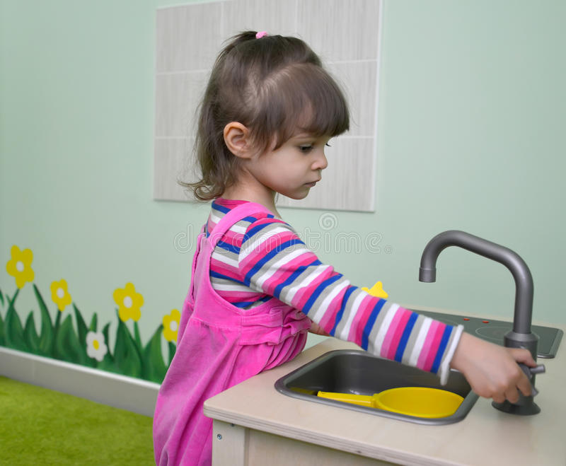 Los juegos de la niña en la cocina de los niños kindergarten foto de archivo libre de regalías