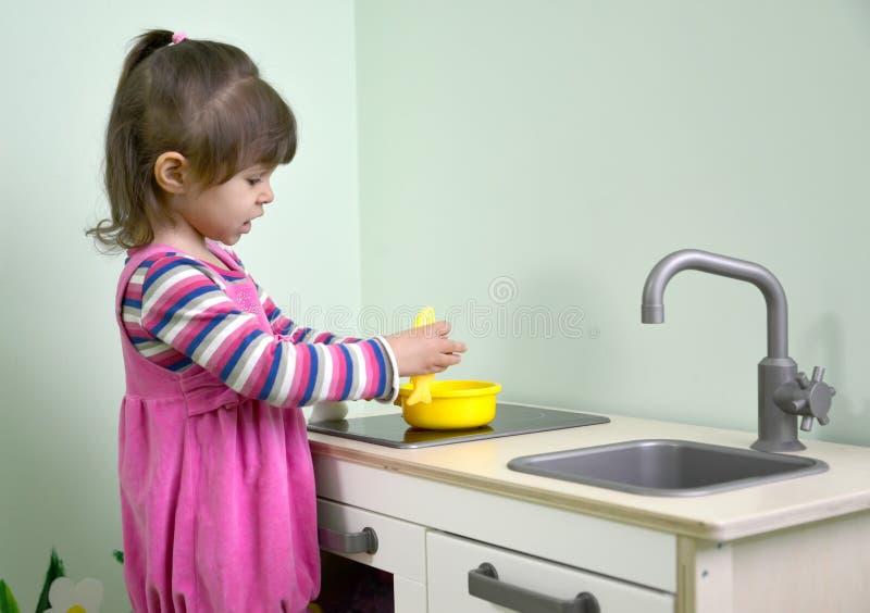 Los juegos de la niña en la cocina de los niños kindergarten imágenes de archivo libres de regalías