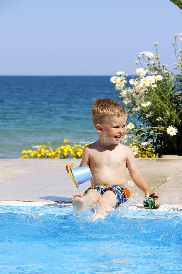 Los juegos de niños acercan a la piscina Mar y flores en el fondo imagenes de archivo