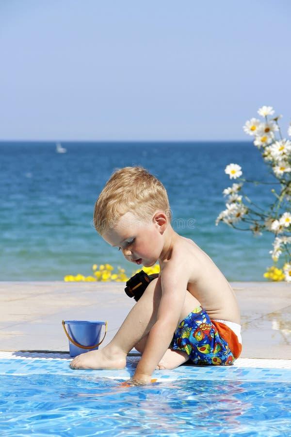 Los juegos de niños acercan a la piscina Mar y flores en el fondo imagen de archivo