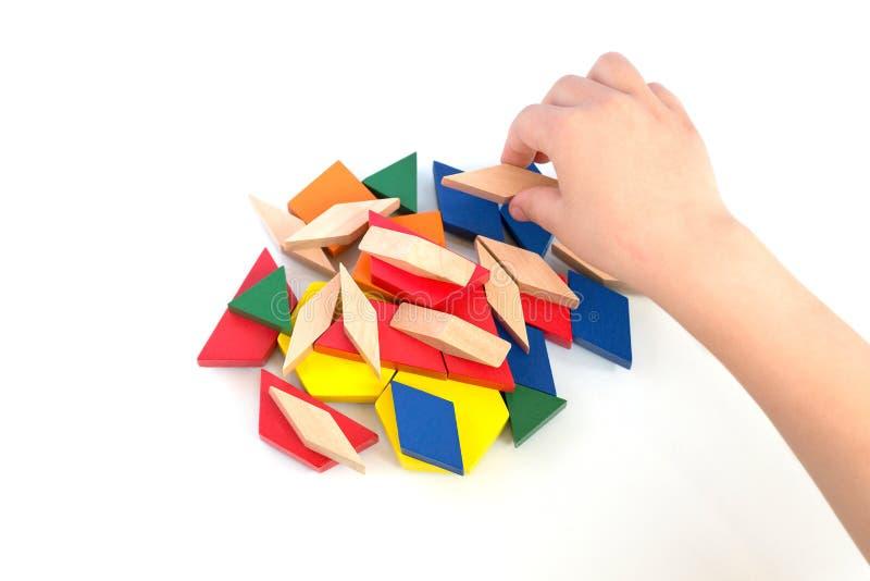 Los juegos de niños con los bloques coloreados construyen un modelo en un fondo de madera ligero imagen de archivo libre de regalías