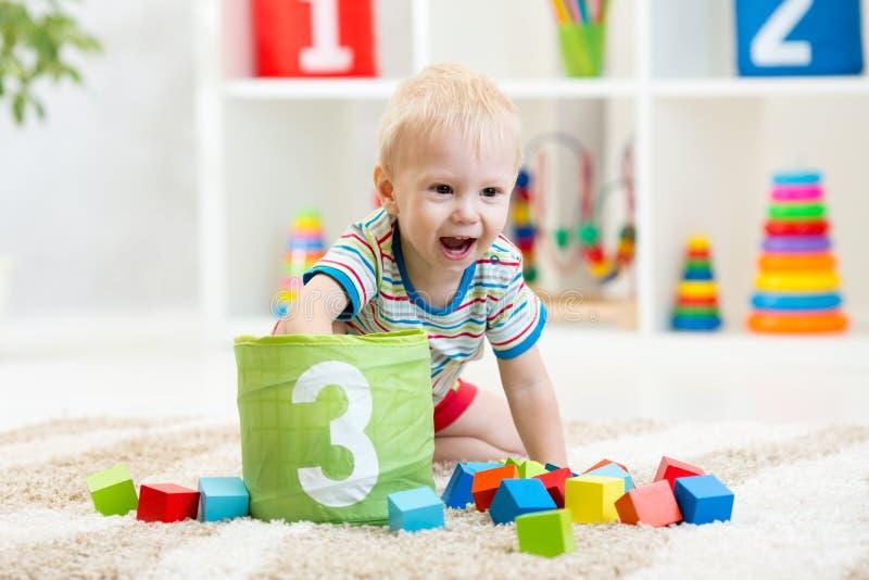 Los juegos de niños del cuarto de niños juegan los cubos en la alfombra acogedora dentro foto de archivo libre de regalías