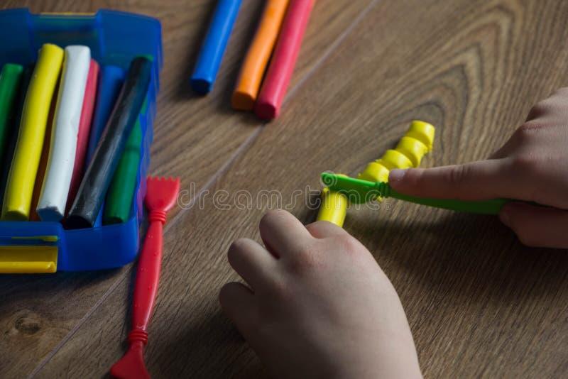 Los juegos de niños en un plasticine multicolor en una tabla de madera Creativo con los niños imagenes de archivo