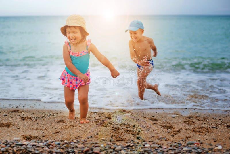 Los juegos de niños y salpican en el mar fotos de archivo libres de regalías