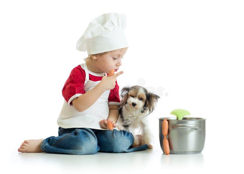 Los juegos lindos del niño pequeño cocinan con los perros divertidos aislados foto de archivo
