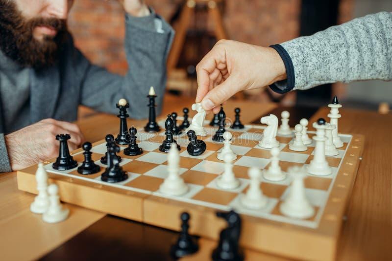 Los jugadores de ajedrez masculinos, el caballero blanco toman el empeño fotos de archivo