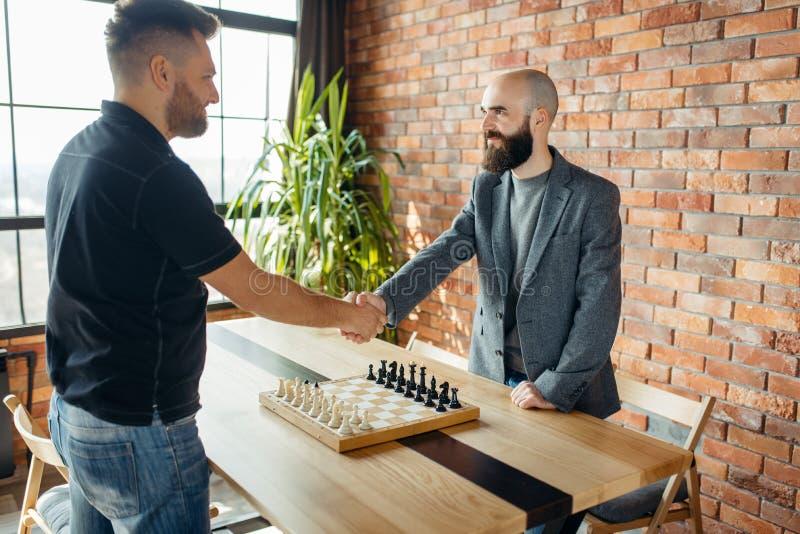 Los jugadores de ajedrez sacuden las manos antes del juego fotos de archivo libres de regalías