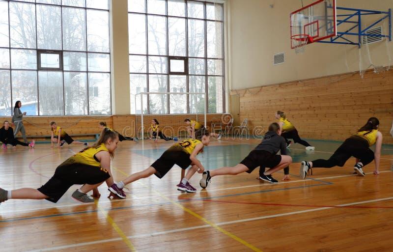 Los jugadores de básquet de las muchachas calientan antes de participar en competencias de la ciudad imagenes de archivo