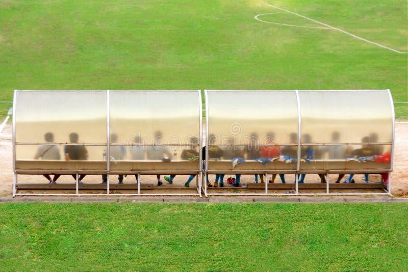 Los jugadores de fútbol y el personal se sientan en banco al lado del campo de fútbol fotografía de archivo libre de regalías