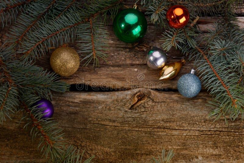 Los juguetes de la Navidad y las ramas del árbol encendieron la vela foto de archivo