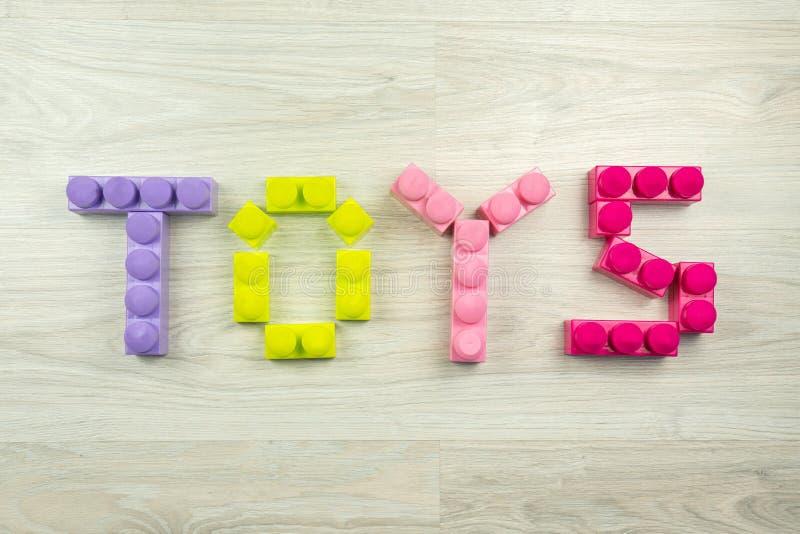 Los juguetes de la palabra deletreados en un fondo de madera imagen de archivo libre de regalías
