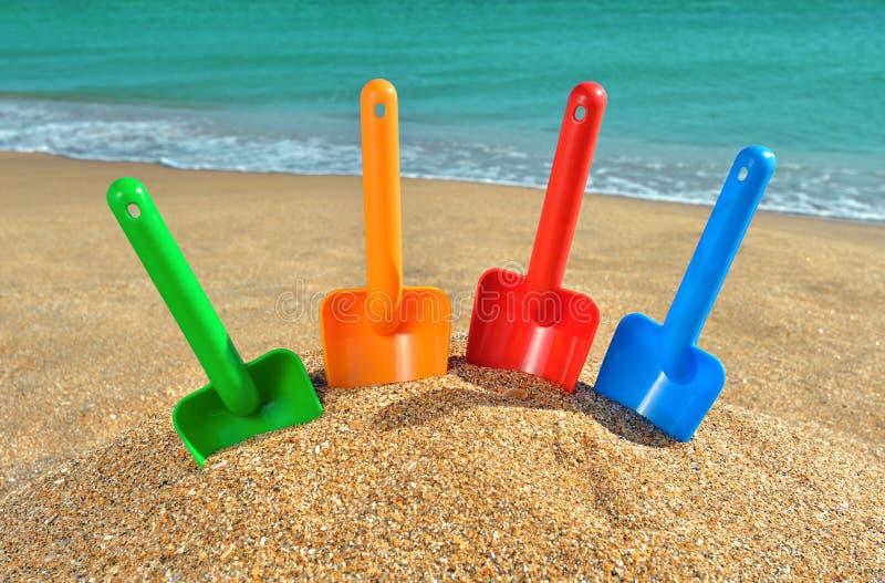 Los juguetes de los niños multicolores en la playa foto de archivo libre de regalías