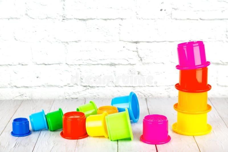 Los juguetes de los niños plásticos en la tabla de madera en un backgrou de la pared de ladrillo fotos de archivo