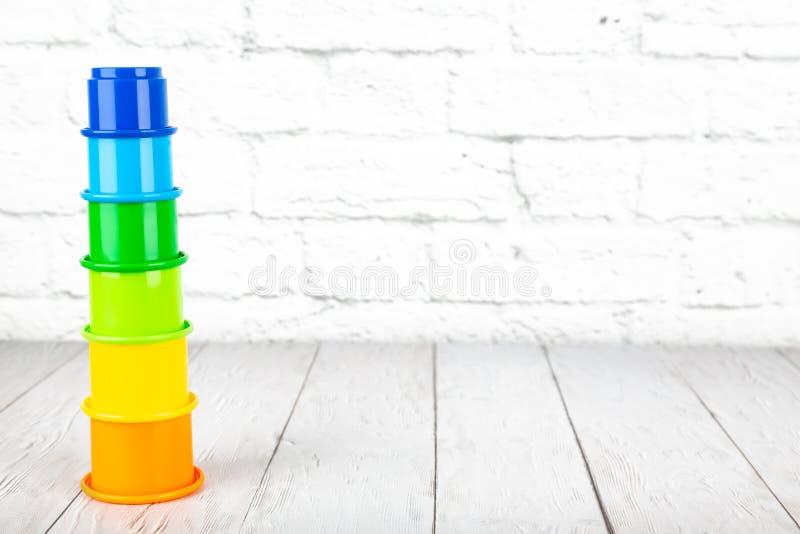Los juguetes de los niños plásticos en la tabla de madera en un backgrou de la pared de ladrillo imagen de archivo
