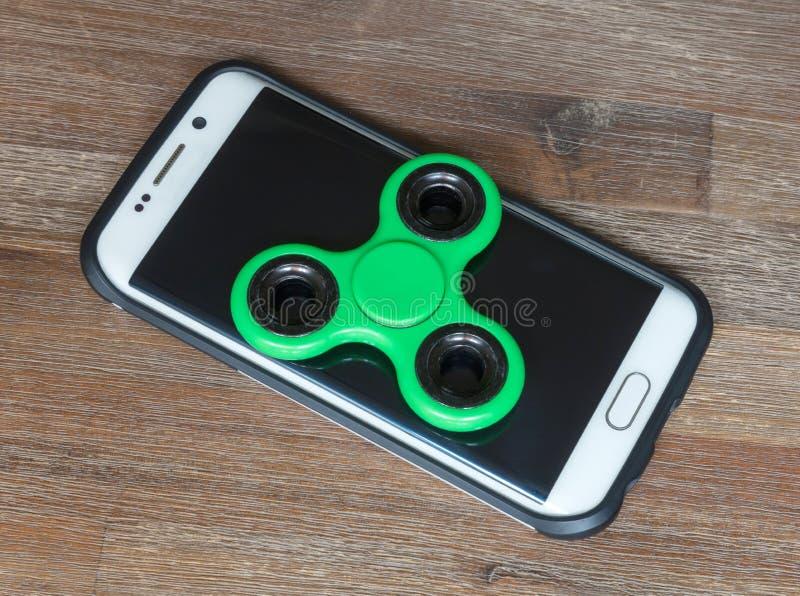 Los juguetes de los niños; Smartphone con un hilandero en el top fotografía de archivo libre de regalías