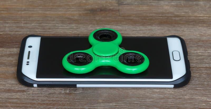 Los juguetes de los niños; Smartphone con un hilandero en el top fotos de archivo