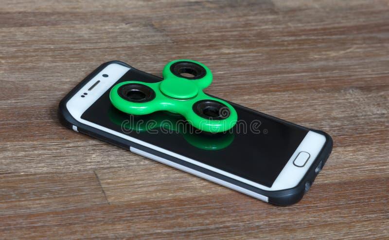 Los juguetes de los niños; Smartphone con un hilandero en el top imagenes de archivo