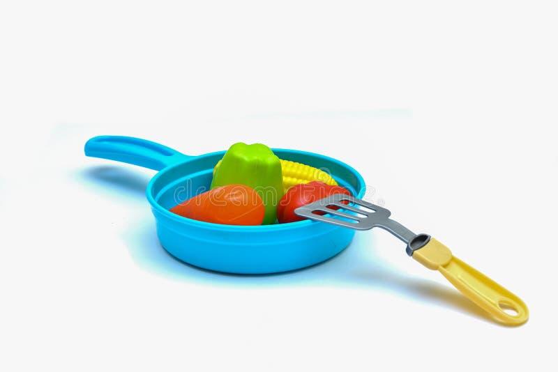 Los juguetes de los niños - un sartén plástico, 4 verduras y un omóplato en un fondo blanco imagen de archivo libre de regalías