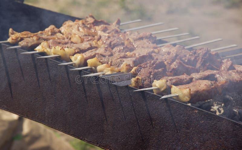 Los kebabs se fríen en la parrilla en el aire abierto fotografía de archivo