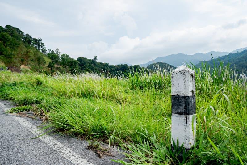 Los kilómetros blancos y negros del pilar concreto de las piedras en el camino se cubren con la hierba Con un cielo gris, kilómet fotografía de archivo libre de regalías