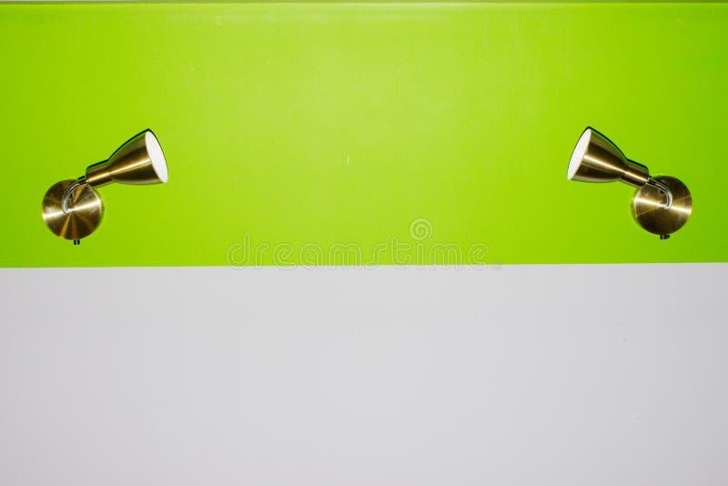 Los lámpara-apliques del metal que colgaban en una superficie verde clara lisa dirigida en uno a localizaron en el centro separac foto de archivo libre de regalías