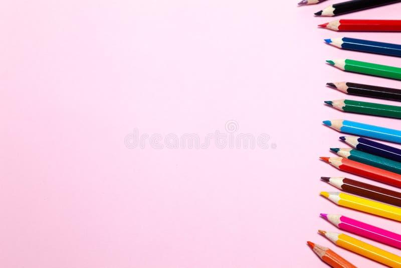 Los lápices coloreados inconsútiles del arco iris reman con la onda en un lado más bajo, varios arreglos, en el papel rosado Conc foto de archivo libre de regalías