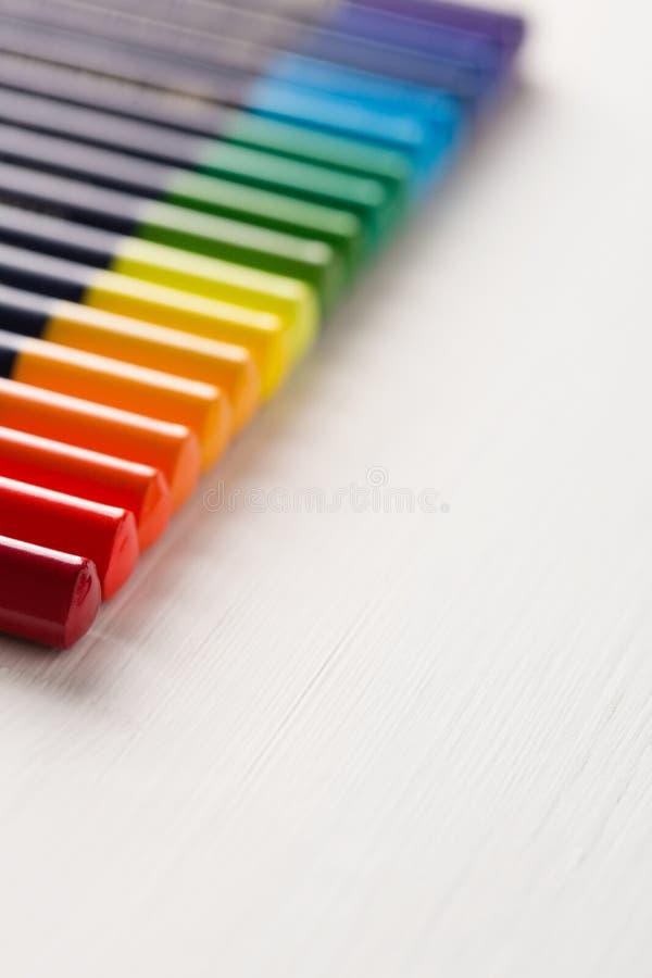 Los lápices coloreados mienten en fila imagenes de archivo