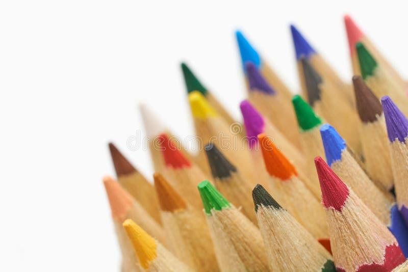 Los lápices del color aislados en el cierre blanco del fondo encima del tiro macro de la pila del lápiz del color dibujan a lápiz foto de archivo