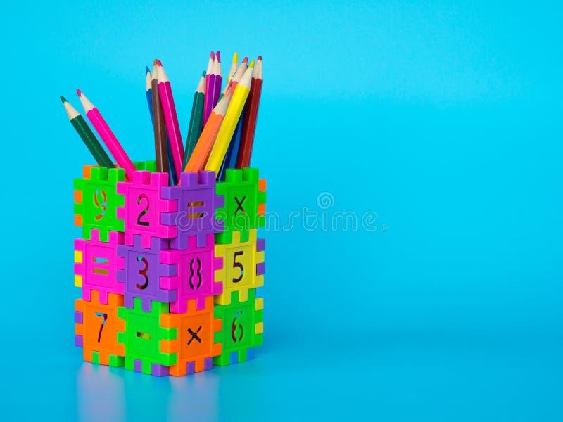 Los lápices del color en colorido del tenedor del lápiz hacen número del rompecabezas de la forma en fondo azul Concepto de educa fotos de archivo