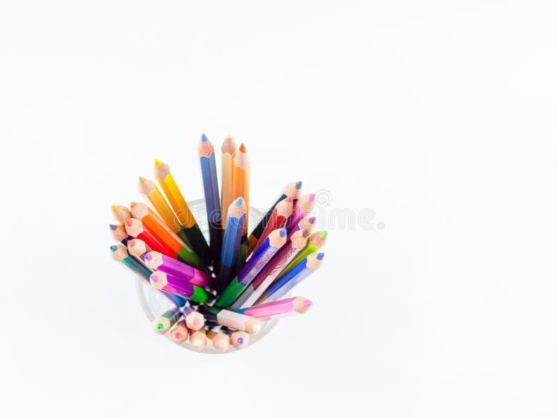 Los lápices del color están en un vidrio en el fondo blanco, visión superior, fotografía de archivo