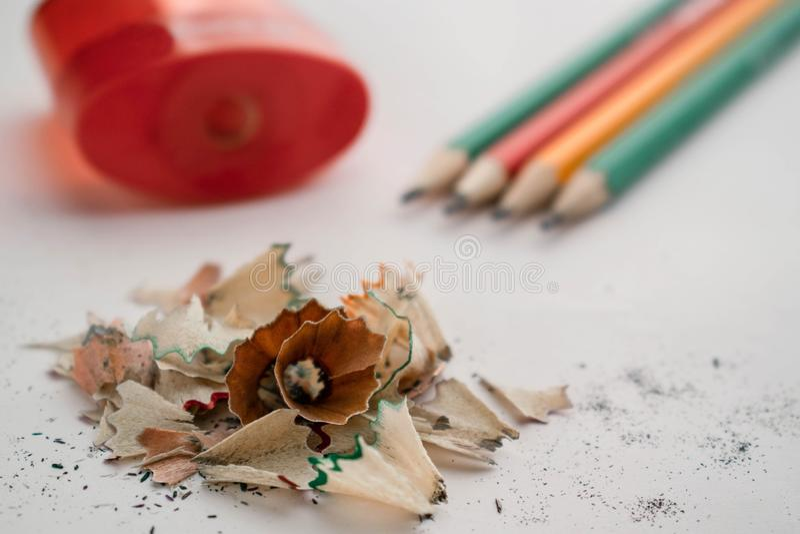 Los lápices del color llenan del serrín y de los sacapuntas rojos en un fondo blanco foto de archivo
