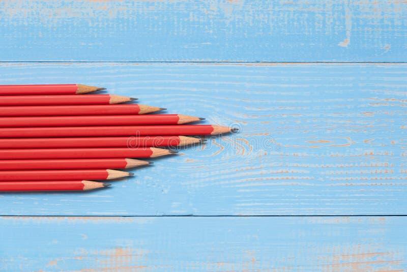 Los lápices rojos de la flecha forman en fondo de madera azul foto de archivo