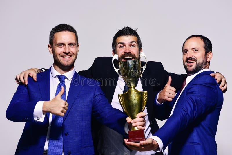 Los líderes de la compañía detienen el premio, los pulgares de la demostración y el abrazo de oro foto de archivo