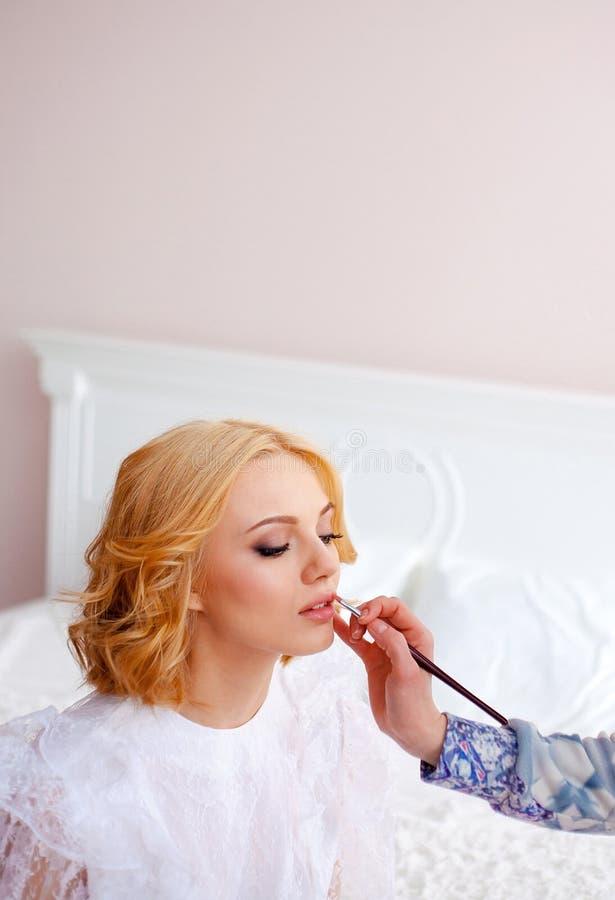 Los labios del modelo del colorete del artista de maquillaje, cierre para arriba imagenes de archivo