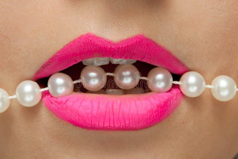 Los labios femeninos con el lápiz labial y las perlas rosados roscan. imagenes de archivo