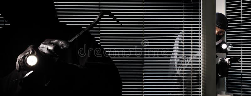 Los ladrones del ladrón del ladrón se están rompiendo en la casa, con la antorcha, la palanca y el arma en ventana negra de la pu imagen de archivo