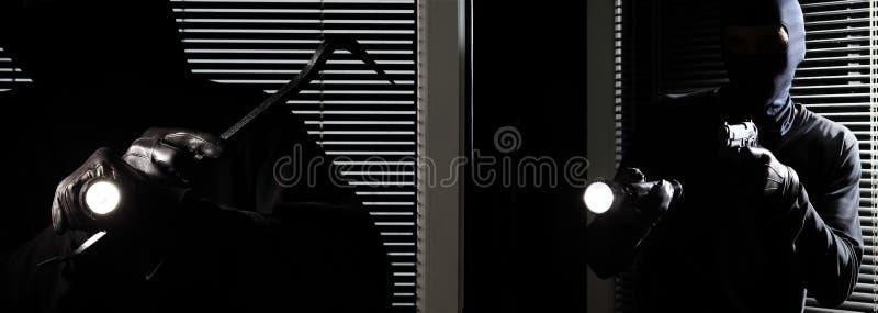 Los ladrones del ladrón del ladrón se están rompiendo en la casa, con la antorcha, la palanca y el arma en ventana negra de la pu fotografía de archivo libre de regalías