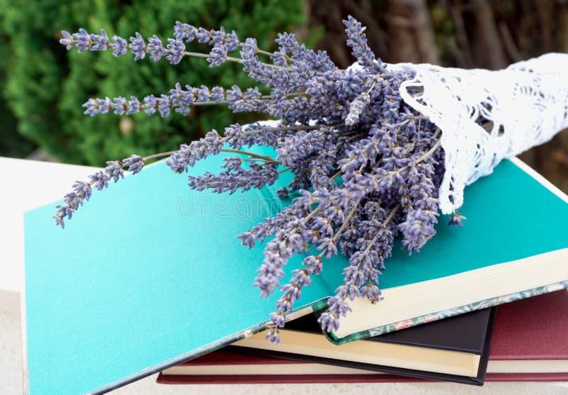 Los libros apilados y en rematan el libro abierto adornado con el manojo de lavanda fotos de archivo libres de regalías